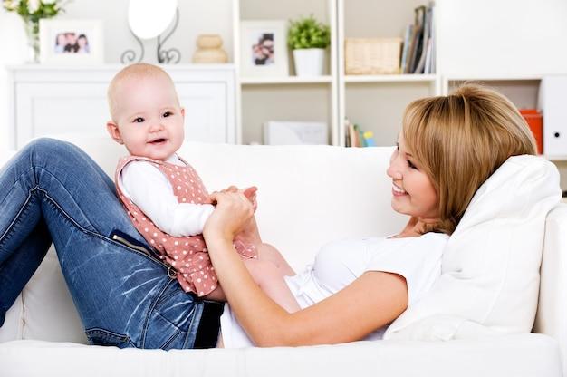 Retrato de uma jovem mãe feliz com um bebê recém-nascido em casa
