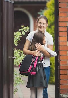 Retrato de uma jovem mãe feliz conhecendo sua filha depois na escola em frente a casa