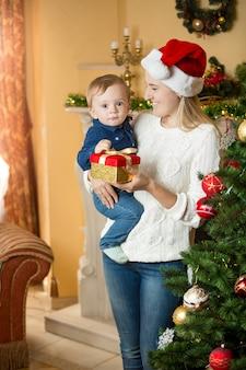 Retrato de uma jovem mãe feliz dando uma caixa de presente para seu bebê no natal