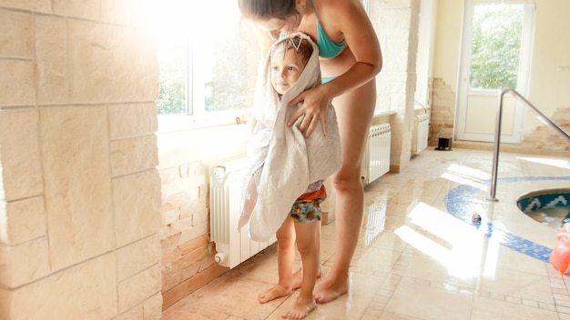 Retrato de uma jovem mãe feliz e sorridente, limpando e aquecendo seu filho pequeno com uma grande toalha branca depois de nadar na piscina