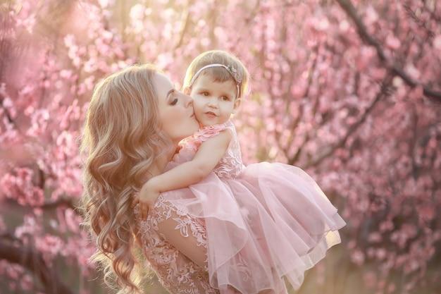 Retrato de uma jovem mãe linda com sua filhinha. close-up ainda de amar a família. mulher atraente, segurando seu filho em flores cor de rosa e sorrindo