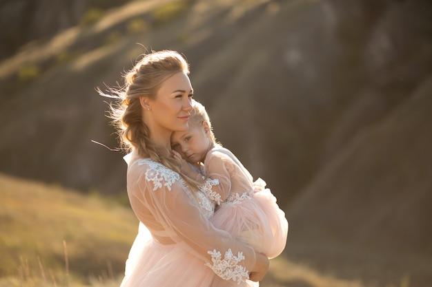 Retrato de uma jovem mãe linda mantém sua amada filha nos braços. amor parental, princesinha