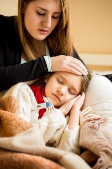 Retrato de uma jovem mãe preocupada verificando a temperatura da filha doente