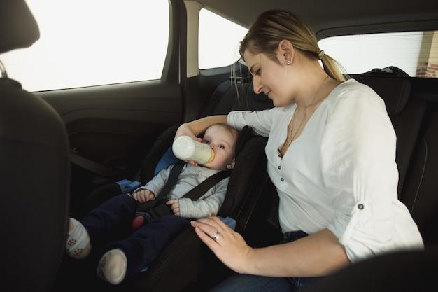 Retrato de uma jovem mãe sorridente alimentando um bebê no carro
