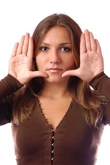Retrato de uma jovem magnífica com maquiagem natural, cabelos castanhos compridos, ela mostra as palmas das mãos perto do rosto
