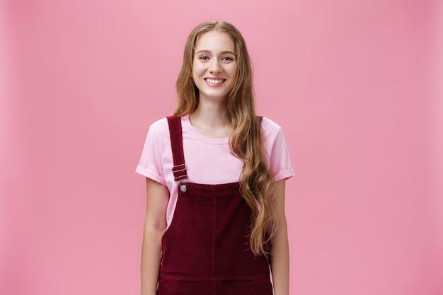 Retrato de uma jovem magro encantadora com cabelo longo loiro em um macacão de veludo cotelê sorrindo alegremente em pé com um sorriso positivo posando contra um fundo rosa feliz e amigável.