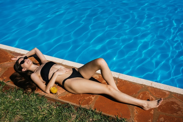 Retrato de uma jovem magro tomando banho de sol perto da piscina do hotel.