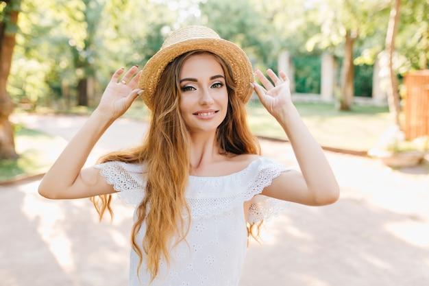 Retrato de uma jovem maravilhosa com longos cabelos loiros, posando com as mãos para cima. menina encantadora com chapéu vintage e vestido branco, sorrindo, aproveitando o sol.