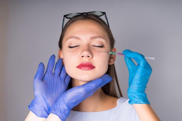 Retrato de uma jovem médica com uma seringa perto do rosto, olhos fechados, outro homem segurando suas mãos com a cabeça