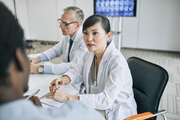 Retrato de uma jovem médica conversando com colegas na mesa de reunião durante uma conferência médica