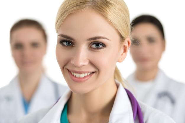 Retrato de uma jovem médica loira rodeada pela equipe médica, olhando e sorrindo. conceito de cuidados de saúde e medicina.