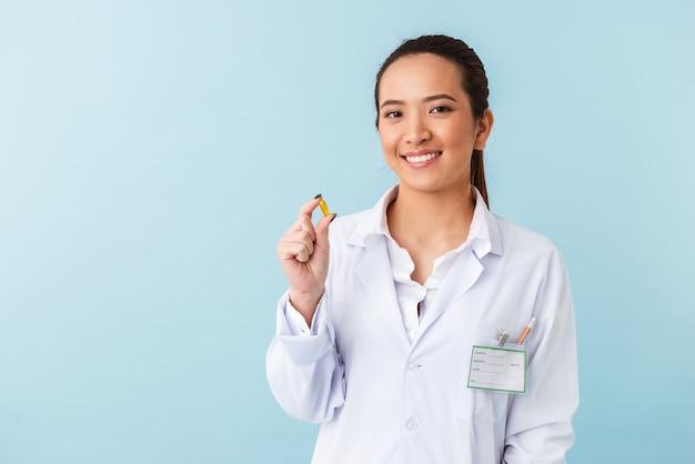 Retrato de uma jovem médica posando isolado sobre a parede azul segurando comprimidos.