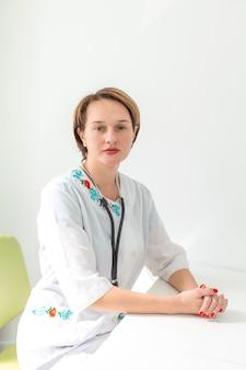 Retrato de uma jovem médica profissional com cabelo curto, em uma sala bem iluminada