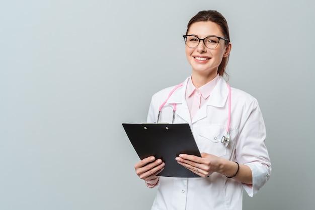 Retrato de uma jovem médica simpática e sorridente, imagem de uma médica de óculos e com um