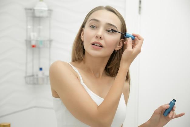 Retrato de uma jovem menina colocando rímel