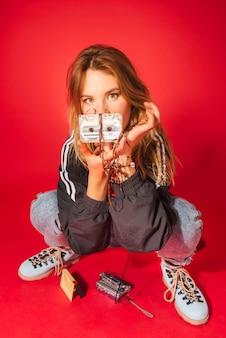 Retrato de uma jovem menina loira em roupas de estilo retrô dos anos 90