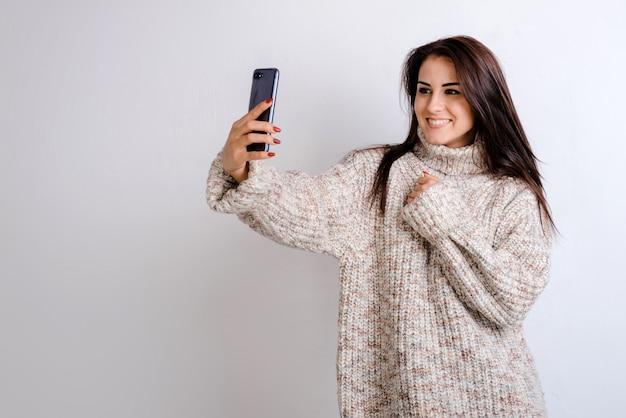 Retrato de uma jovem menina morena bonita elegante faz selfies em estúdio, ela vestida com uma camisola quente.