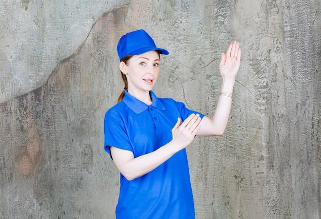 Retrato de uma jovem mensageira de uniforme azul mostrando um gesto de golpe de caratê