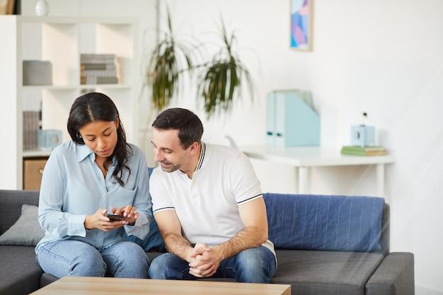 Retrato de uma jovem mestiça mostrando smartphone para um colega enquanto está sentado no sofá no interior do escritório