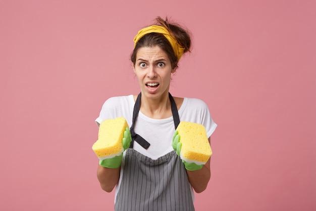 Retrato de uma jovem mimada usando bandana, avental e luvas de borracha verdes se sentindo frustrada, pois ela tem que fazer toda a limpeza sozinha, segurando esponjas nas mãos e parecendo confusa