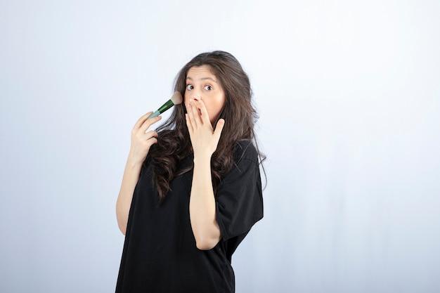Retrato de uma jovem modelo aplicando maquiagem com pincel na parede branca.