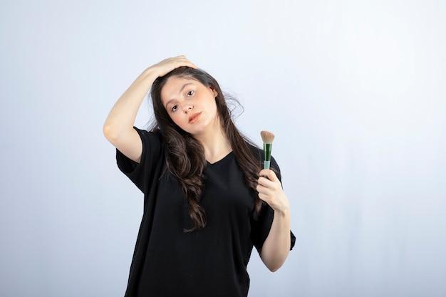 Retrato de uma jovem modelo com maquiagem com pincéis em pé na parede branca.