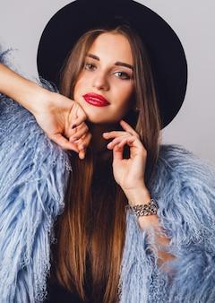 Retrato de uma jovem modelo com um casaco fofo de inverno elegante e chapéu preto posando
