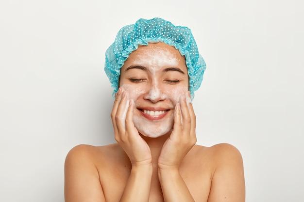 Retrato de uma jovem modelo encantada aplica espuma de limpeza facial, toca as bochechas, tem a pele perfeita e limpa após o banho, limpa os poros