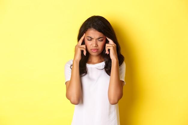 Retrato de uma jovem modelo feminina afro-americana se sentindo mal, franzindo a testa e tocando a cabeça, reclamando