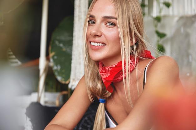 Retrato de uma jovem modelo feminina e bonita e descontraída com bandana vermelha no pescoço, tem seu próprio estilo, sentada no interior aconchegante do café