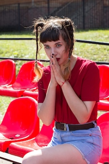 Retrato de uma jovem modelo normal e linda garota tennager nos assentos de um estádio de beisebol usando uma camiseta vermelha