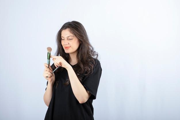 Retrato de uma jovem modelo olhando para o pincel de maquiagem na parede branca.