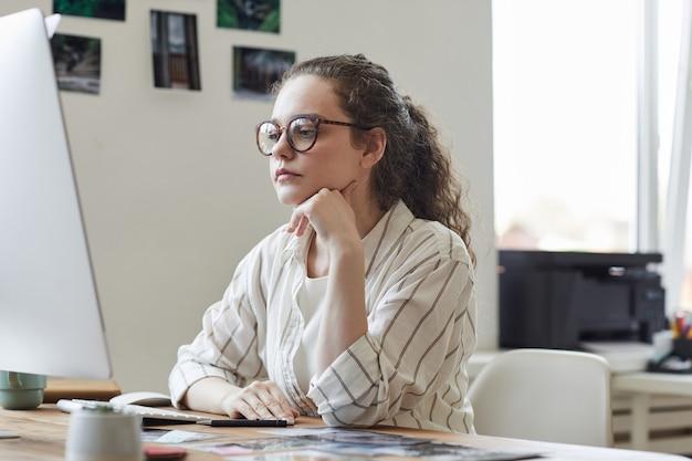 Retrato de uma jovem moderna de óculos, olhando pensativamente para a tela do computador enquanto trabalha na mesa de um escritório branco, copie o espaço