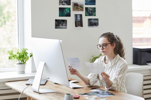 Retrato de uma jovem moderna segurando fotografias para publicação enquanto trabalhava no pc no escritório branco, copie o espaço