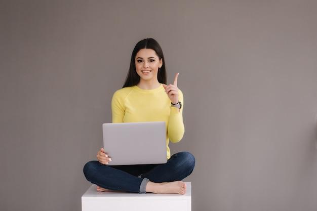 Retrato de uma jovem morena animada, segurando o computador laptop e comemorando o sucesso isolado sobre o fundo cinza.