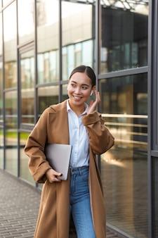Retrato de uma jovem morena asiática usando fones de ouvido segurando um laptop enquanto caminha pela rua da cidade