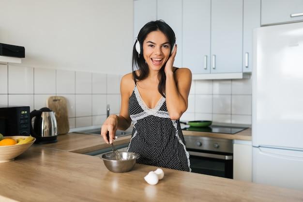 Retrato de uma jovem morena atraente cozinhando ovos mexidos na cozinha de manhã, sorrindo, humor feliz, dona de casa positiva, estilo de vida saudável, ouvindo música em fones de ouvido