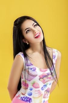 Retrato de uma jovem morena atraente em uma blusa rosa em uma mulher engraçada amarela com cabelo escuro