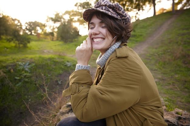 Retrato de uma jovem morena atraente feliz com penteado casual, tocando suavemente seu rosto com a mão levantada enquanto sorri agradavelmente com os olhos fechados, sentado no jardim da cidade