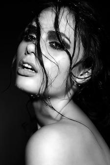 Retrato de uma jovem morena bonita com cabelo e pele molhada