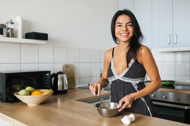 Retrato de uma jovem morena bonita cozinhando ovos mexidos na cozinha pela manhã, sorrindo, humor feliz, dona de casa positiva, estilo de vida saudável