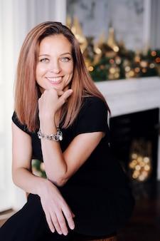 Retrato de uma jovem morena com um lindo sorriso, cabelos longos em roupas pretas, perto da árvore de natal