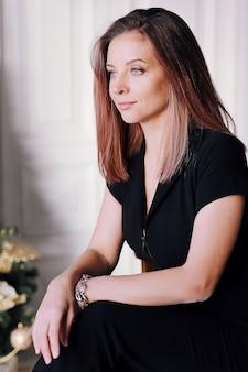 Retrato de uma jovem morena com um lindo sorriso, cabelos longos em roupas pretas