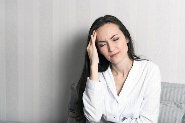 Retrato de uma jovem morena de pijama, sentado na cama, dor de cabeça, enxaqueca