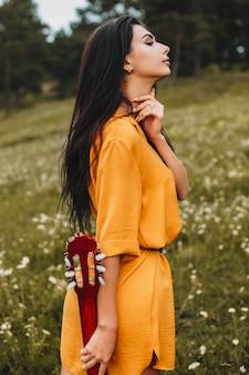 Retrato de uma jovem morena encantadora com cabelos longos, olhando para longe segurando uma quitar. jovem músico caminhando na natureza cantando.