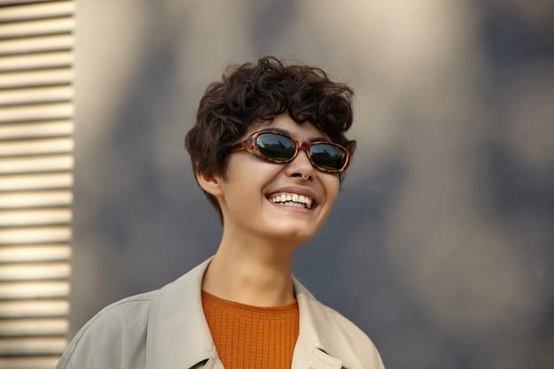 Retrato de uma jovem morena encantadora com corte de cabelo curto, sorrindo alegremente em pé sobre o ambiente urbano em roupas elegantes e óculos de sol vintage