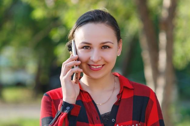 Retrato de uma jovem morena feliz com um smartphone na mão, levantada para a orelha dela. menina falando no celular e sorrindo. filmado em um dia ensolarado