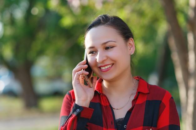 Retrato de uma jovem morena feliz com um smartphone na mão, levantada para a orelha dela. menina falando no celular e sorrindo.