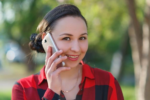 Retrato de uma jovem morena feliz com um telefone na mão, levantada para a orelha dela. menina falando no celular e sorrindo. filmado em um dia ensolarado