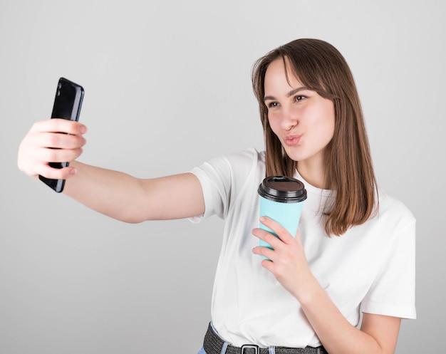 Retrato de uma jovem morena feliz com uma blusa branca, segurando um copo azul de café para viagem e se beijando